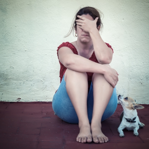 Sad adult woman crying with a small dog besides her. Are you stressing out your dog?